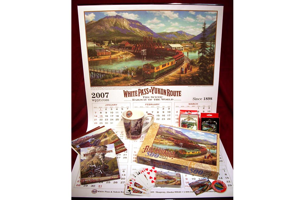WP&YR products – Shows a sampling of retail products featuring a painting of a White Pass & Yukon Route train in Carcross, YT, Canada. Calendar, mug, note cards, ornaments, playing cards and puzzle.